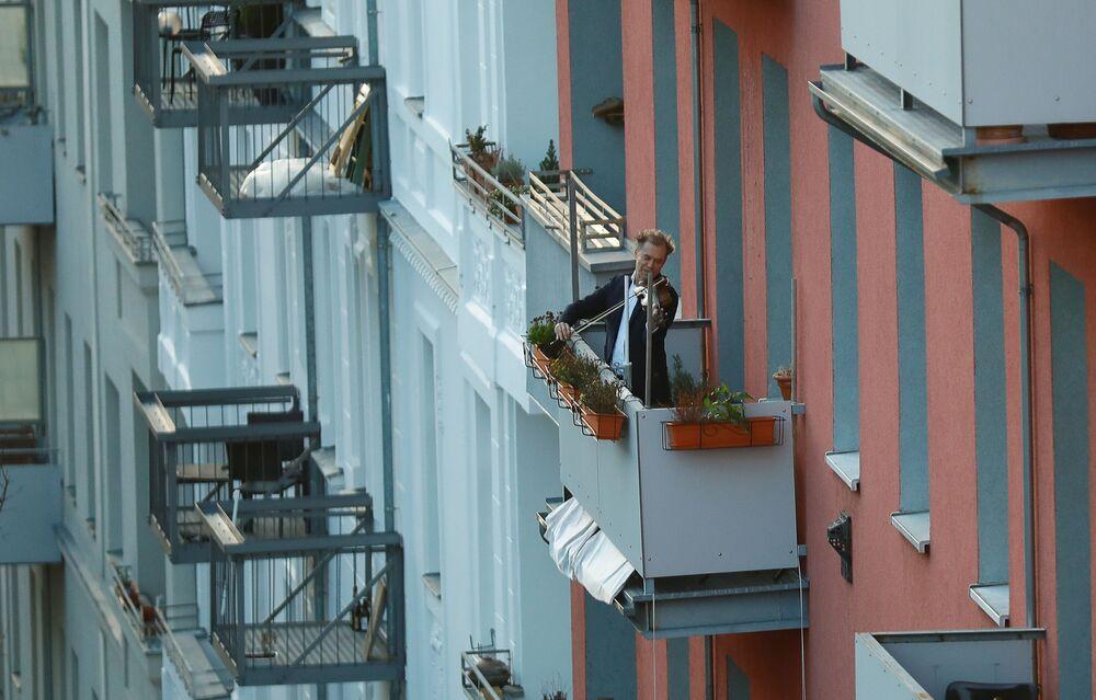 Muž hraje na housle na balkóně v Berlíně