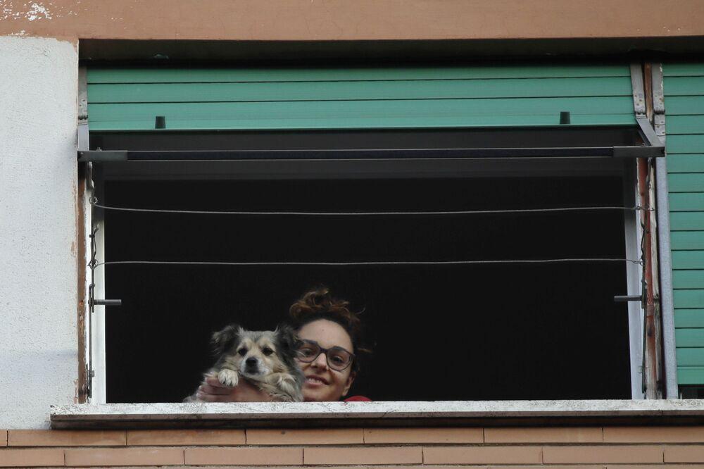 Dívka se svým psem vyhlíží z okna. Řím, Itálie