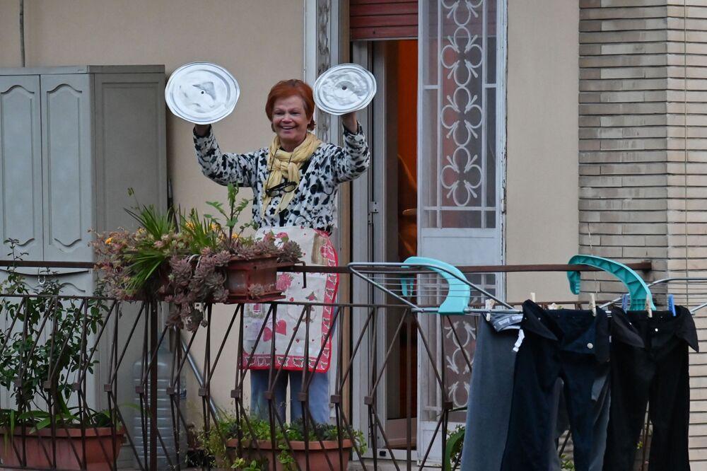 Žena s hrnci se účastní akce Podívej se z okna. Řím, Itálie
