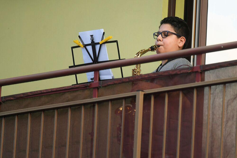 Chlapec hraje na saxofon na balkóně ve městě Milán, Itálie