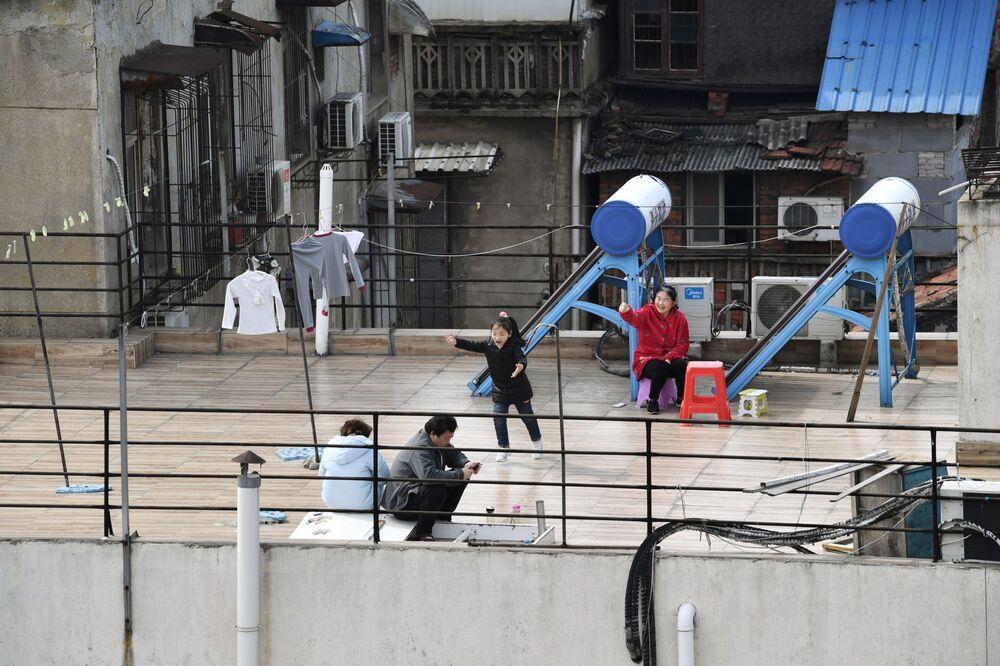 Lidé sedí na střeše domu. Wu-chan, Čína