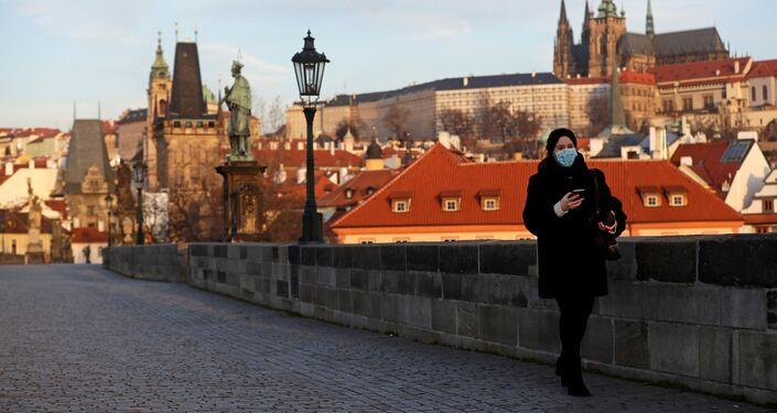 Žena v roušce stojící na prázdném Karlově mostě