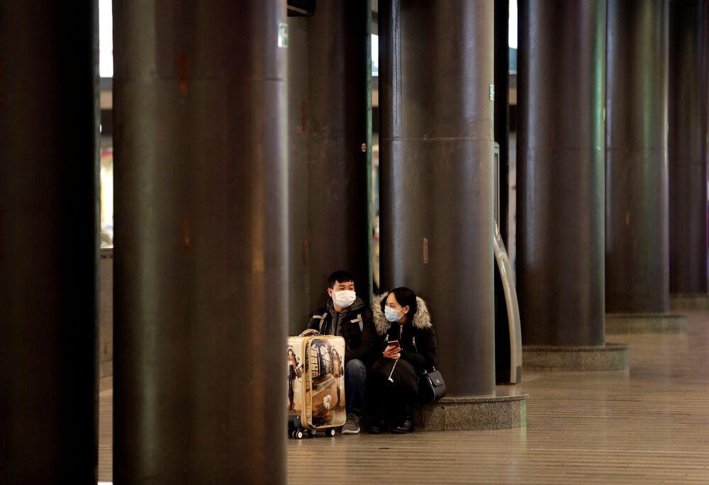 Cestující v rouškách na železniční zastávce