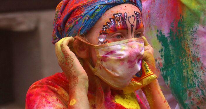 Turista v roušce během oslav festivalu Hólí v Puškar, Indie