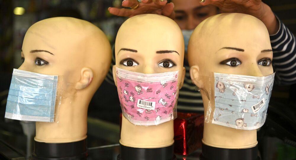 Manekýnky v rouškách ve výloze obchodu v Bogotě