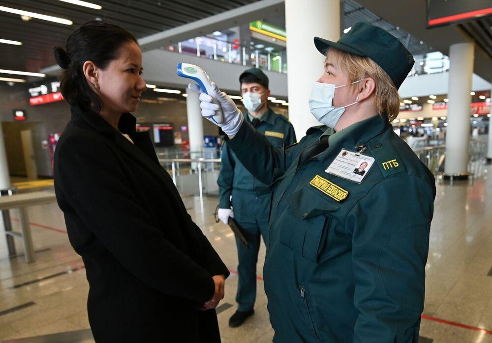 Zaměstnanec dopravní bezpečnostní služby měří teplotu cestujícího na vlakovém nádraží lázeňského města Soči, rajon Adler