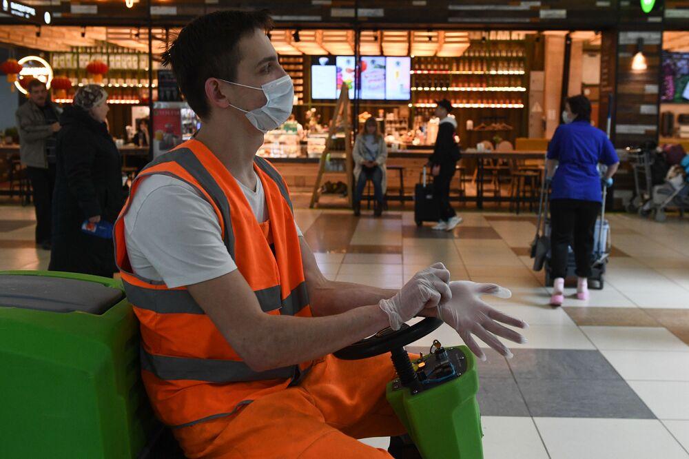Zaměstnanec čistící služby nosí ochrannou roušku na letišti Tolmačevo v Novosibirsku