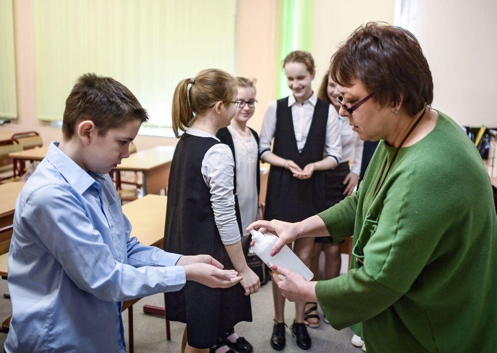 Školní zaměstnankyně nalévá do rukou školáků dezinfekční gel