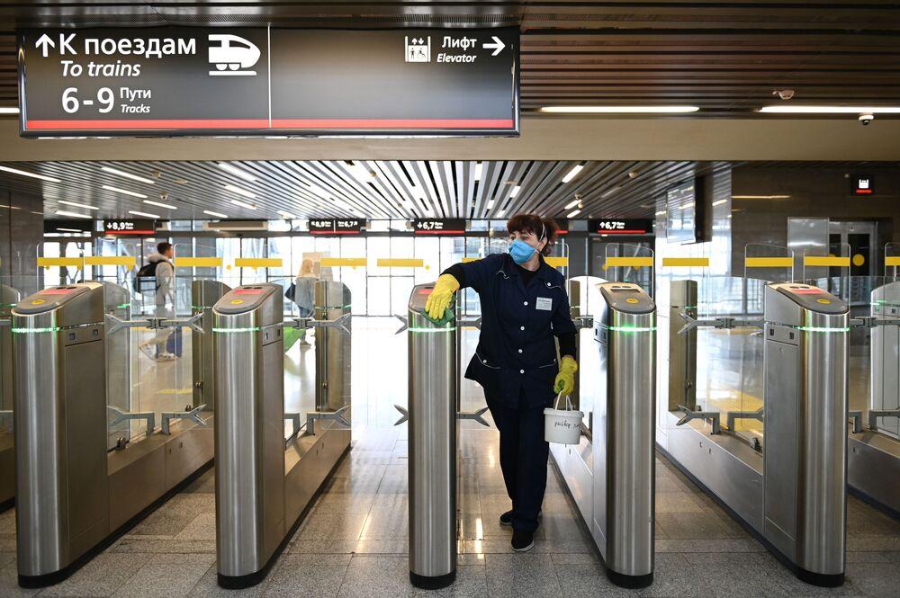 Zaměstnankyně úklidové firmy dezinfikuje turnikety na vlakovém nádraží Adleru