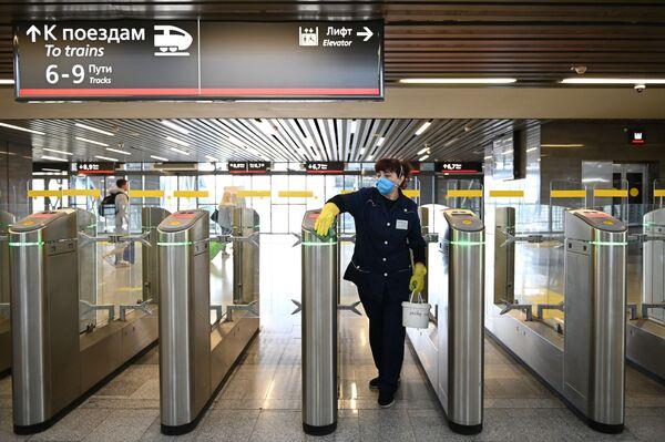 Zaměstnankyně úklidové firmy dezinfikuje turnikety na vlakovém nádraží Adleru - Sputnik Česká republika