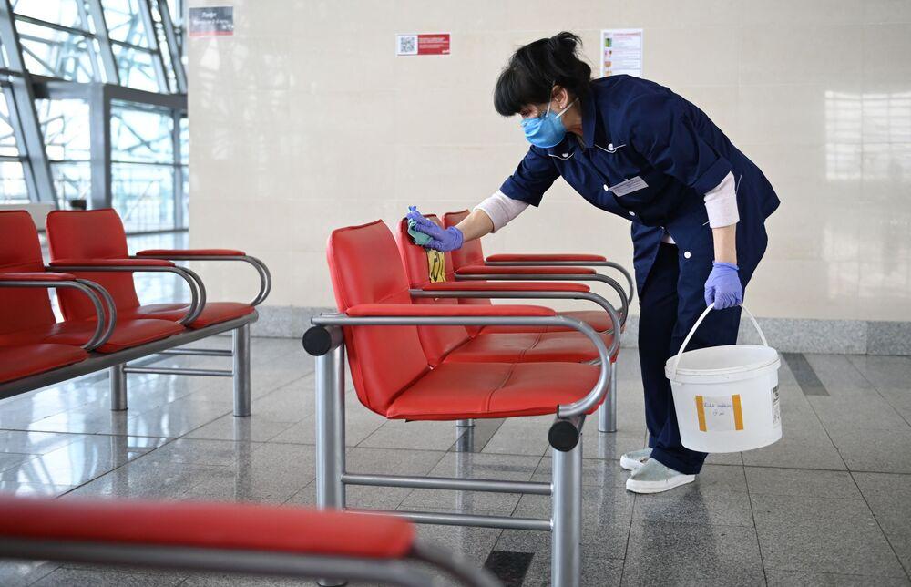 Zaměstnankyně úklidové firmy v ochranné roušce dezinfikuje místa k sezení na vlakovém nádraží Adleru