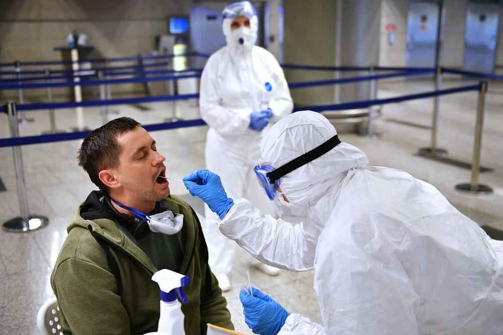 Zdravotnický pracovník kontroluje zdravotnický stav cestujícího na letišti Vnukovo
