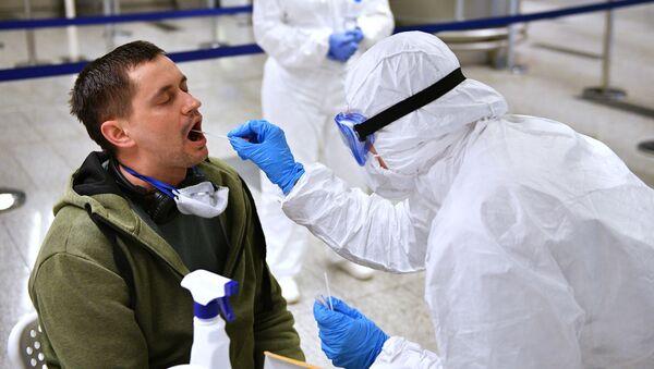 Zdravotnický pracovník vyšetřuje cestujícího. Illustráční foto - Sputnik Česká republika