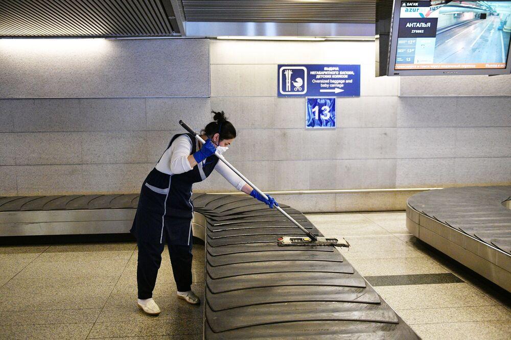 Zaměstnankyně čistící služby uklízí pásku na zavazadlo. Letiště Vnukovo