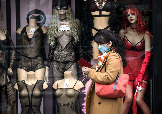 Žena v roušce se prochází kolem výloh uzavřeného obchodu s erotickým zbožím v Paříži, 16. března 2020