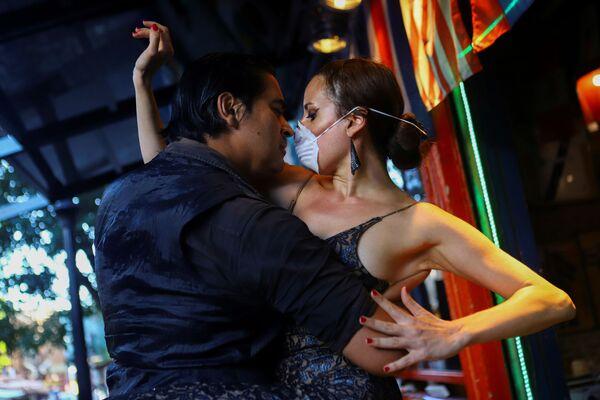 Muž a žena v rouškách tančí tango v téměř prázdné restauraci v Buenos Aires, Argentina, 16. března 2020 - Sputnik Česká republika