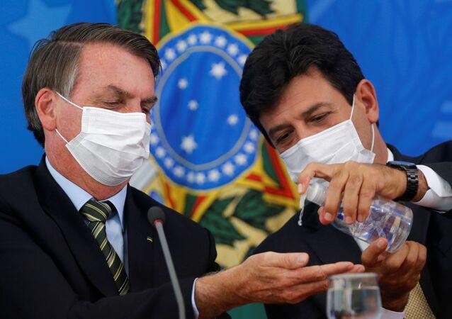 Brazilský prezident Jair Bolsonaro a ministr zdravotnictví Luiz Henrique Mandettas během tiskovky