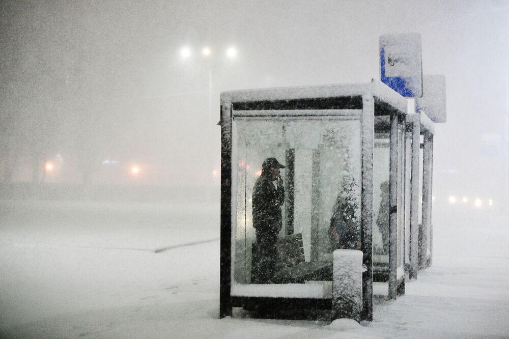 Lidé čekají na zastávce během sněžení v Podolsku, Rusko