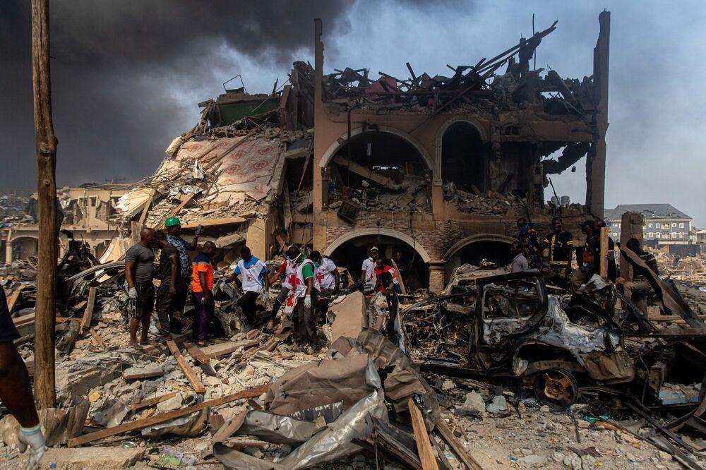 Zástupci Červeného kříže vynášejí oběť výbuchu plynu z budovy v Lagosu, Nigérie