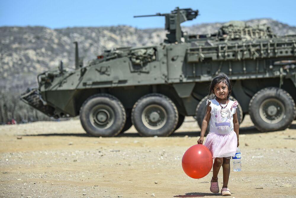 Dívka s červeným balónkem poblíž tanku v Kolumbii
