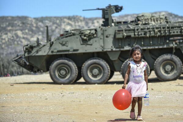 Dívka s červeným balónkem poblíž tanku v Kolumbii - Sputnik Česká republika