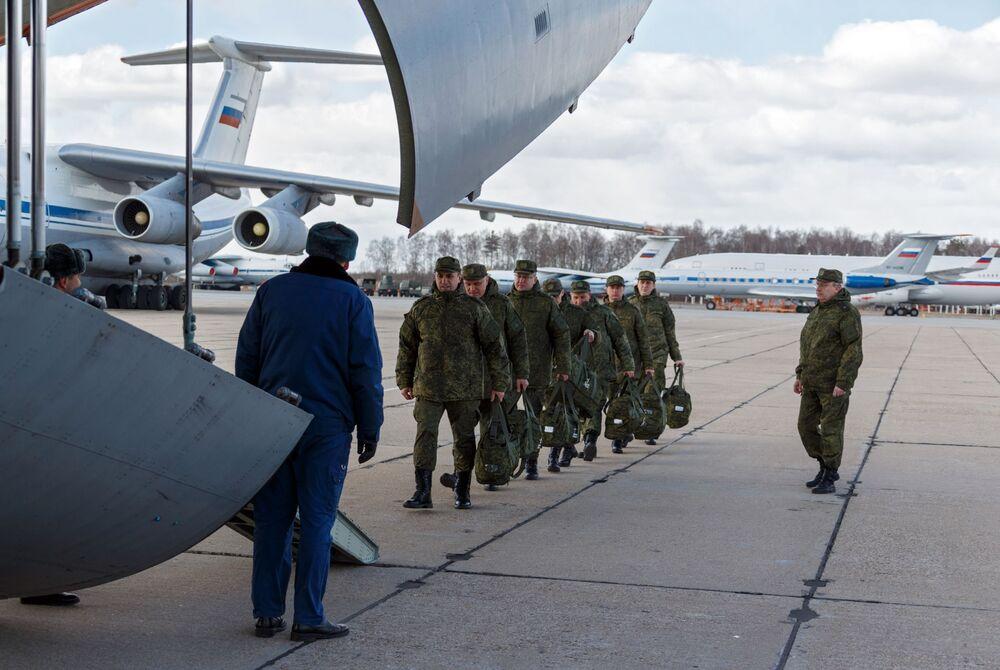 Vojenský personál lékařské služby Ozbrojených sil Ruské federace při nástupu do vojenského transportního letadla ruského letectva Il-76