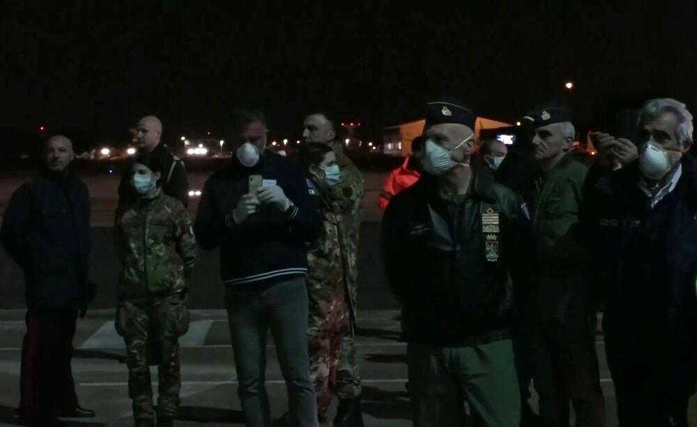 Italský vojenský personál čeká na ruské letadlo se zdravotnickým zařízením na letecké základně Pratica di Mare