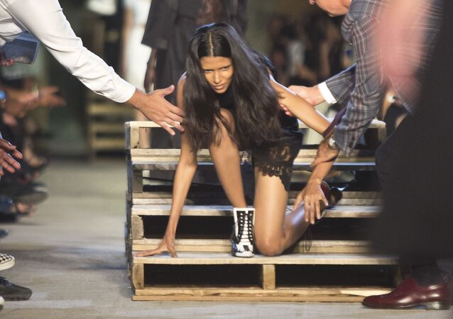 Model vstává po padání na přehlídce Givenchy během New York Fashion Week 2015 v New Yorku.