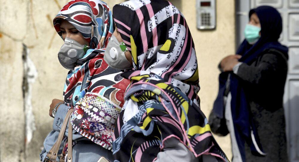 Ženy chodí po jedné z centrálních ulic Teheránu v rouškách