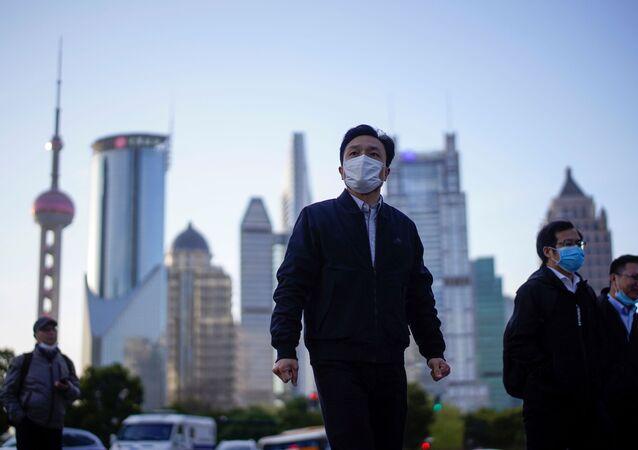 Lidé v rouškách v čínské Šanghaji