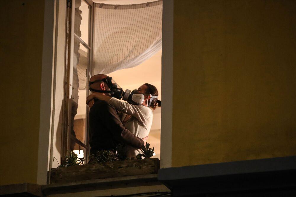 Maskovaný pár v okně domu v Nice, Francie