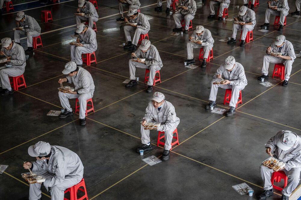 Pracovníci během přestávky na oběd na automobilovém závodě Dongfeng Honda Wuhan, Čína