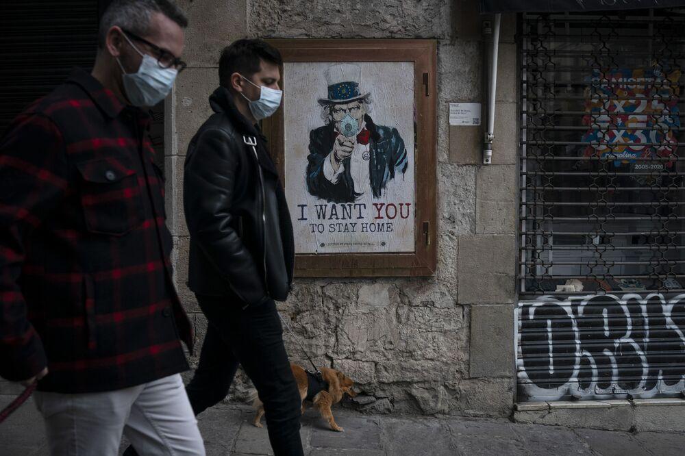 Lidé na ulici v Barceloně na pozadí plakátu umělce TvBoy