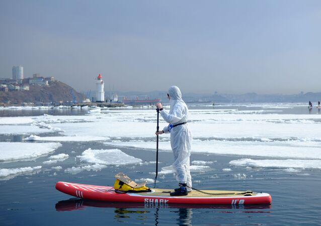 Supsurfař v ochranném obleku v zátoce. Vladivostok, Rusko