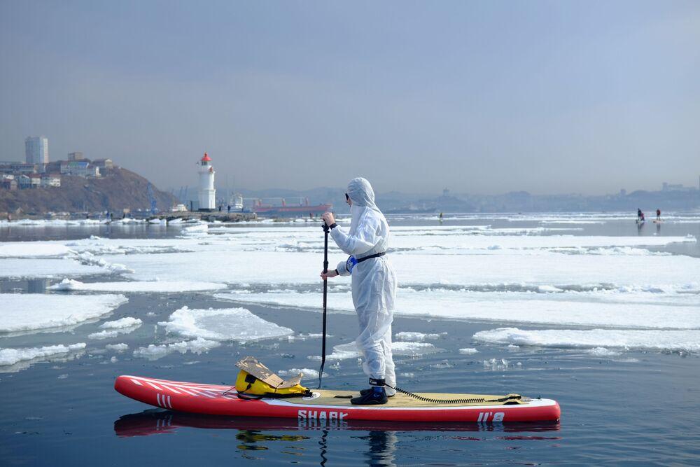 Sapsurfer v ochranném obleku v zátoce Vladivostok