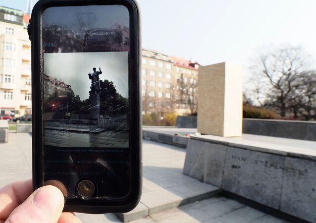 Fotografie pomníku maršálovi SSSR Ivanu Konevoví v Praze na obrazovce telefonu na pozadí náměstí Interbrigády, kde byl demontován