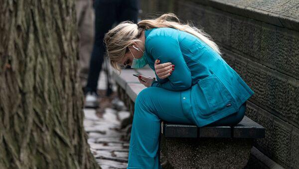 Zdravotnická pracovnice sedí na lavičce poblíž Central Parku, Manhattanská čtvrt v New Yorku, USA, 30. března 2020. - Sputnik Česká republika