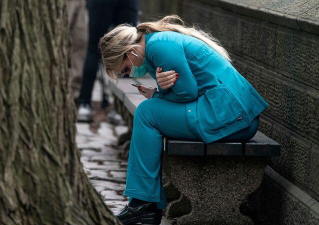 Zdravotnická pracovnice sedí na lavičce poblíž Central Parku, Manhattanská čtvrt v New Yorku, USA, 30. března 2020.