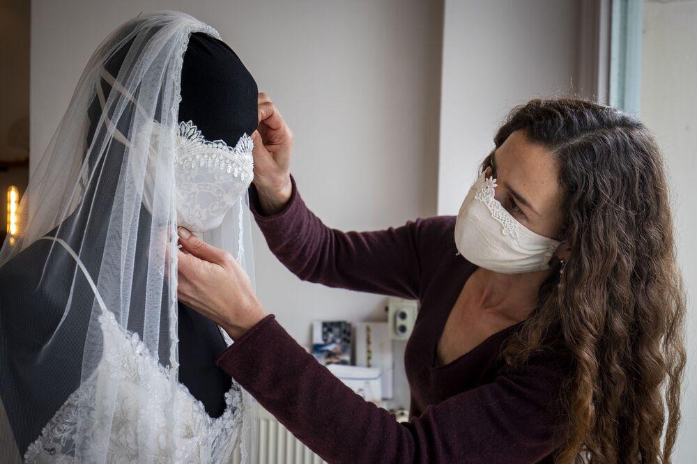 Návrhářka Friederike Jorzigová dokončuje svatební šaty s rouškou. Berlín, Německo