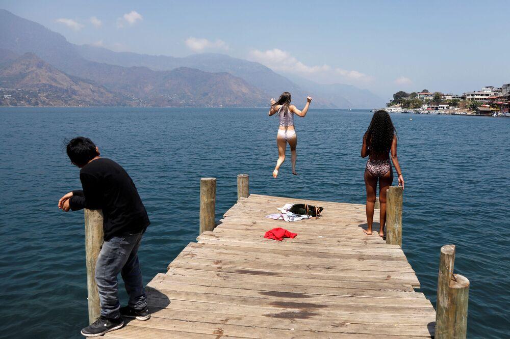 Studentka skáče do vody jezera Atitlán. San Pedro La Laguna, Guatemala.