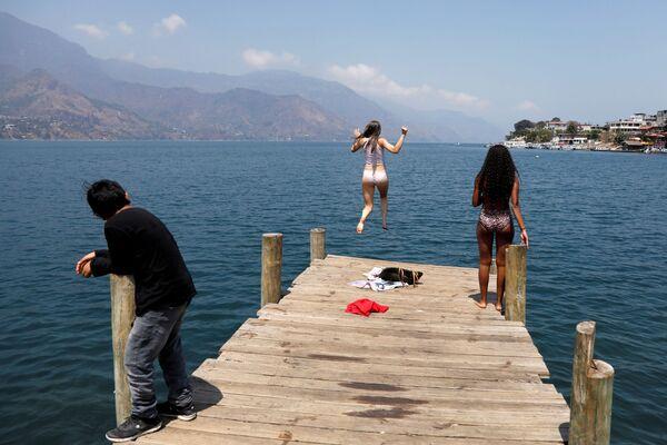 Studentka skáče do vody jezera Atitlán. San Pedro La Laguna, Guatemala. - Sputnik Česká republika