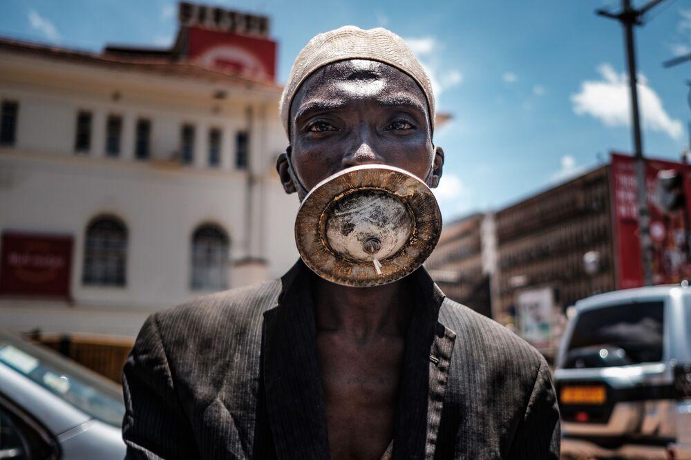 Muž v roušce vlastní výroby. Kampala, Uganda .