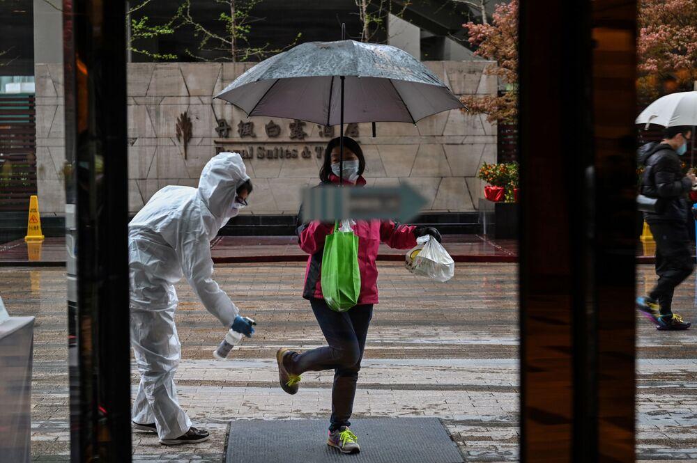 Pracovník hotelu během provádění dezinfekce v čínském Wu-chanu