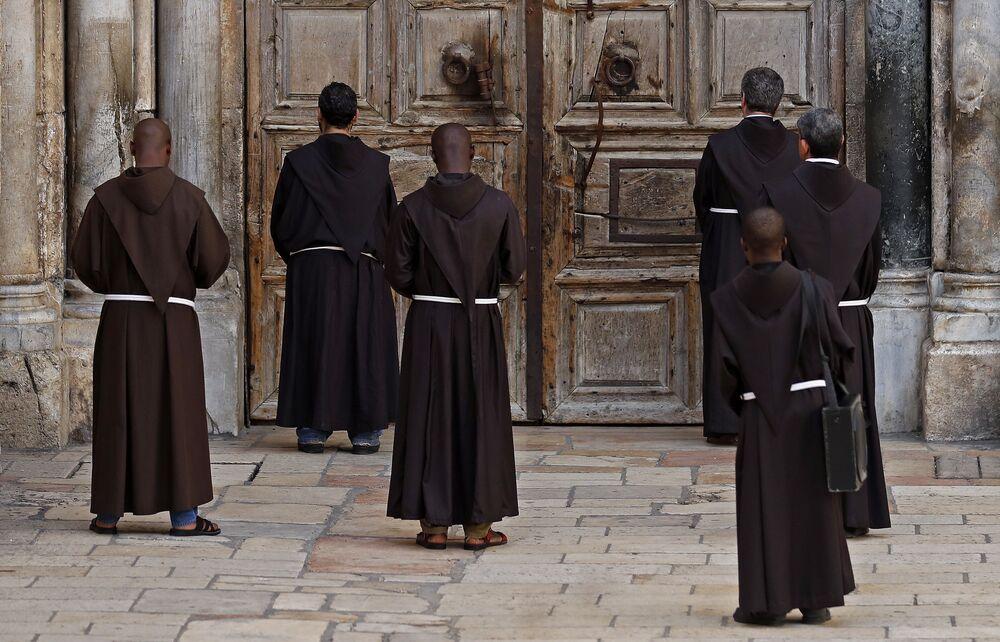 Františkánští mniši během modlitby před zavřenými dveřmi Chrámu Božího hrobu. Jeruzalém, Izrael.