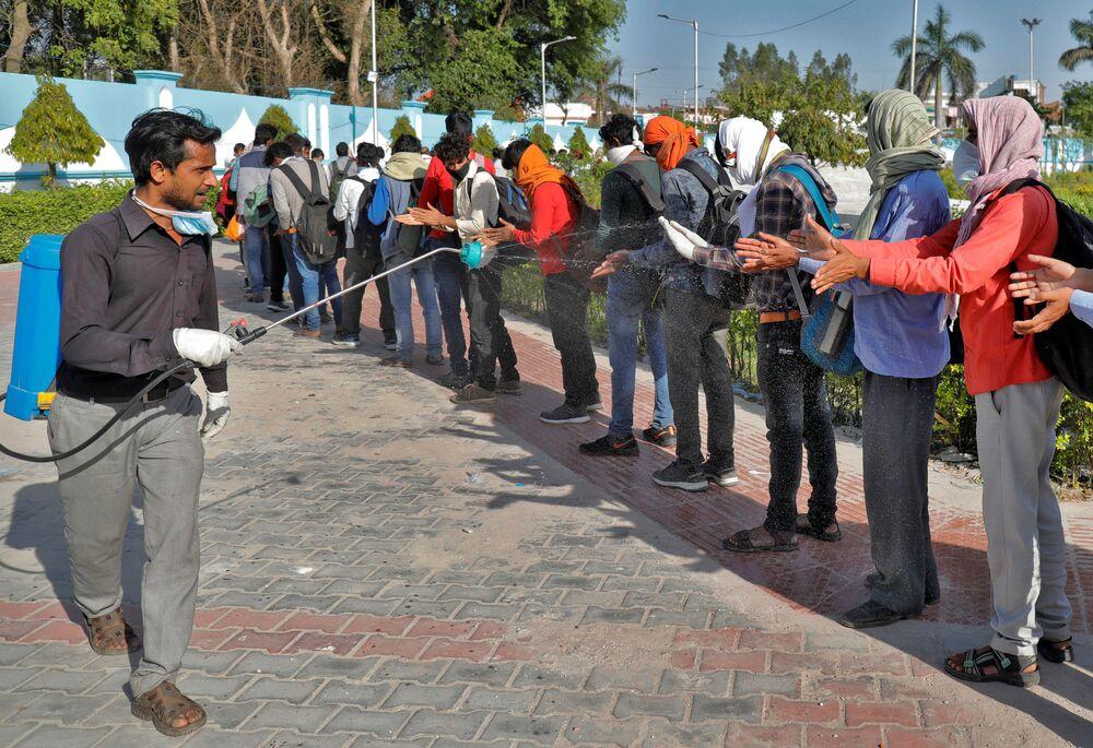 Dezinfekce pracujících migrantů. Lakhnaú, Indie