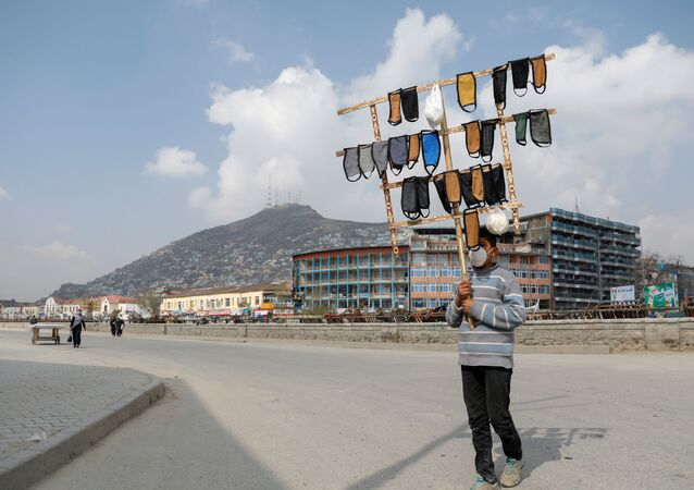 Chlapec prodává roušky v Kábulu.