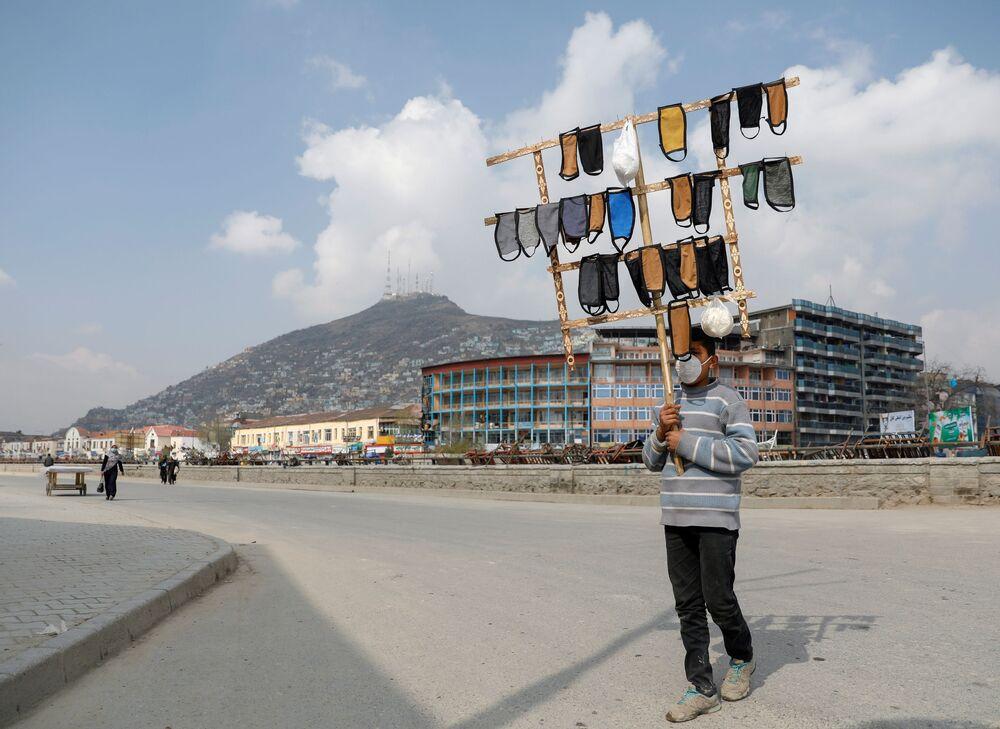 Chlapec prodává roušky v Kábulu