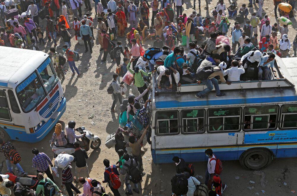 Pracující migranti v přeplněných autobusech. Nové Dillí, Indie