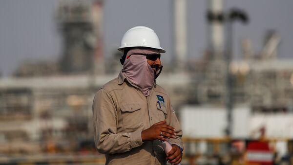 Pracovník na pozadí rafinérie Aramco v Saúdské Arábii  - Sputnik Česká republika