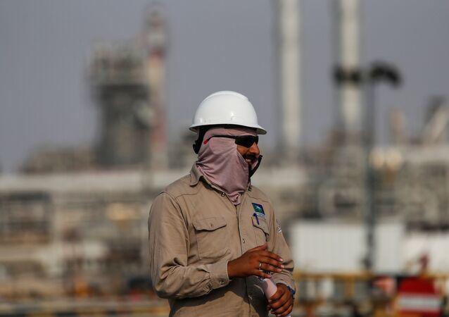 Pracovník na pozadí rafinérie Aramco v Saúdské Arábii